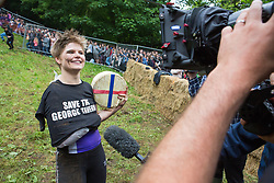 © Licensed to London News Pictures 26/05/2018, brockworth, Gloucester, UK. The annual cheese rolling race held at Coopers Hill, Brockworth outside Gloucester. Competitors race down the extremly steep slippery hill chasing a double Gloucester cheese, the winner of each race recieves the cheese as thier prize. Pictured here :  The winner of the ladies race Flo Early from Stroud with her prize cheese - Photo Credit : Stephen Shepherd/LNP