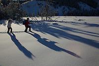 Russell Laman (age 12) and Jessica Laman (age 9)  cross-country skiing below the Teton Range, cast long shadows in the afternoon light.<br />