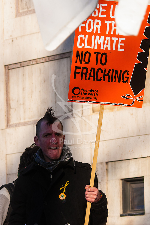 London, March 7th 2015. Following the Climate march through London, masked anarchists and environmental activists clash with police following a breakaway protest at Shell House. PICTURED: An anti-fracking protester with his placard - he was arrested a few minutes later after a confrontation with police.