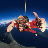 Two skydivers giving thumbs-up in mid-air portrait