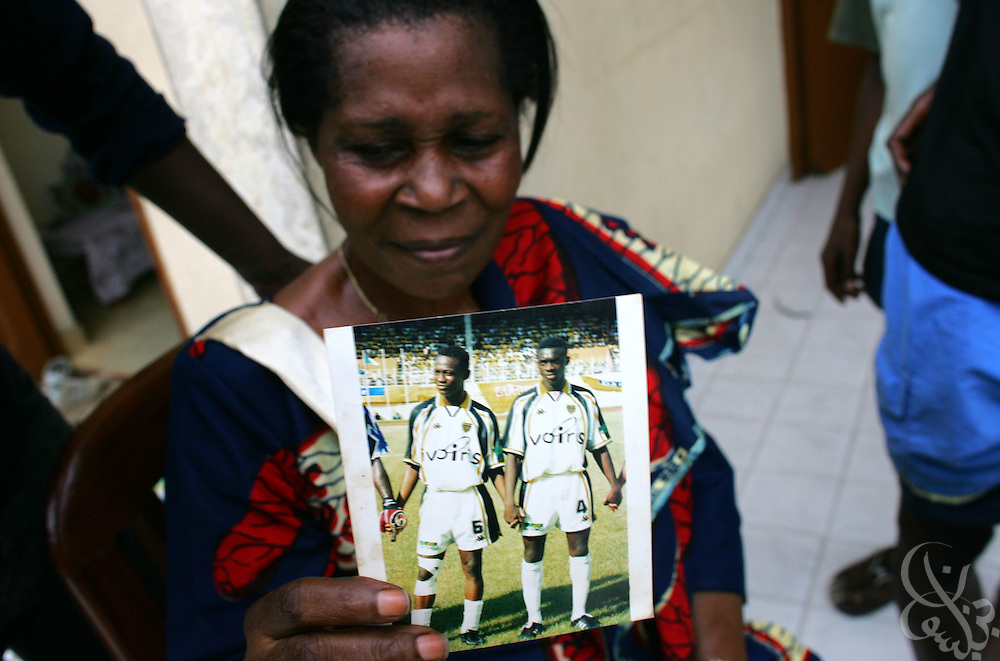 "Alphonsine Zokora, mother of Ivory Coast national team member Didier ""Maestro"" Zokora holds up a picture of her son while looking through her scrapbooks in her home in the Yopoungon neighborhood of Abidjan, Ivory Coast February 18, 2006. Alphonsine has founded a group called the ""mothers of the football playing elephants"" that meets monthly with the other mothers of national team members."