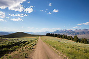 High prairie road in Central Idaho near Mackay with the Lost River Range and Idahos highest peak Mount Borah looming off to the right at 12,667 ft or 3859 meters of elevation