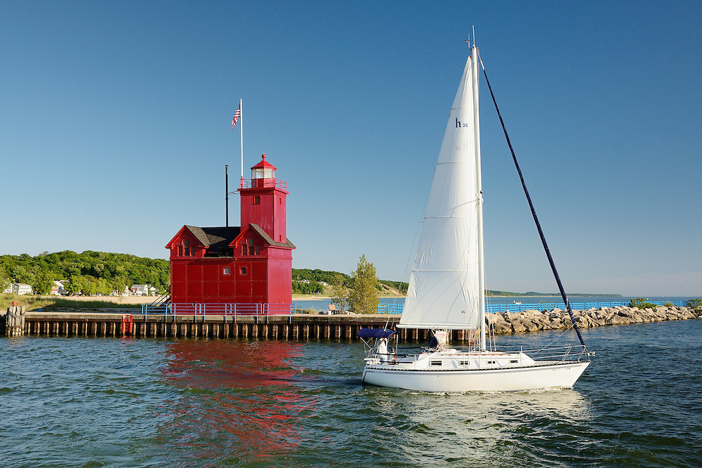 A sailboat heads past Big Red to view the Lake Michigan sunset.<br />
