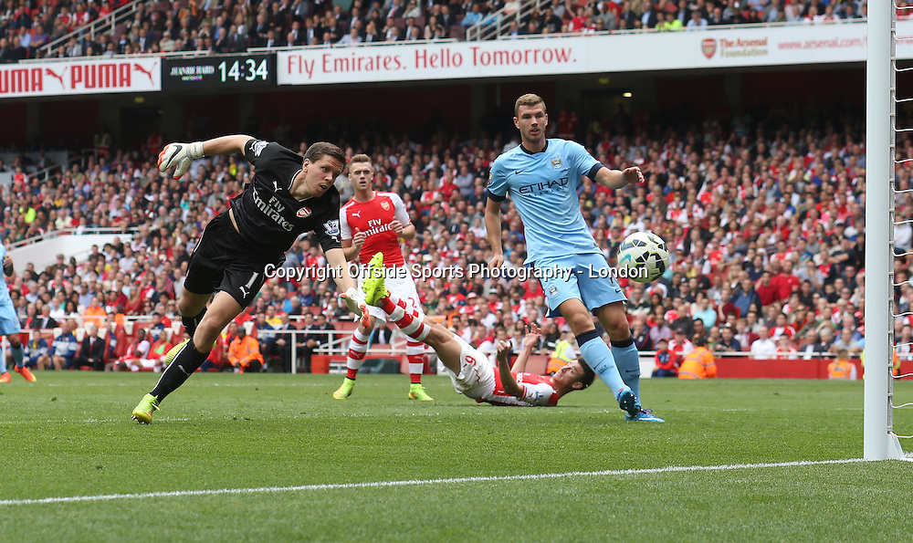 13 September 2014 , Premier League ,  Football Arsenal v Manchester City - A back pass from the fallen Laurent Koscielny of Arsenal goes over the head of his goalkeeper Wojciech Szczesny but hits the goalpost, watched by City striker Edin Dzeko.<br /> Photo: Mark Leech
