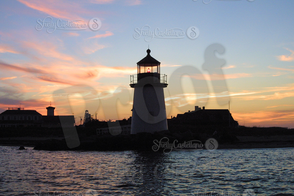 9 September 2001: Scenic view Brant Point lighthouse during sunset from a sailboat during sunset off the shore of Nantucket Island, Cape Cod, MA.  Colorful pink and gold clouds line a blue sky reflecting on the ocean water.