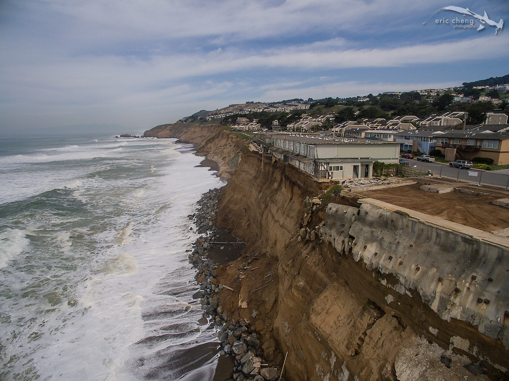 Updated aerial images taken Feb 25, 2016. On January 25, 2016, a state of emergency was declared in Pacifica, California, after king tides and storm surge pummeled the coastline. Many of the apartments in Pacifica are hanging off of soft sandstone cliffs and are in danger of falling off.  Photo taken February 25, 2016.