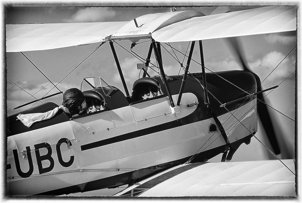 Pilot with leather helmet and a white scarf flapping in the wind on board of a vintage biplane Tiger Moth De Haviland DH 82A (buit in 1938)