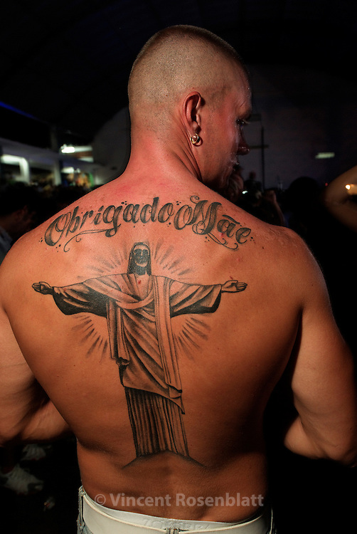 "In the heat of the Baile Funk, a young man shows his tattoo of Christ Redeemer with the phrase ""Thank you mother"". Baile Funk at Boqueirão club, Rio de Janeiro."