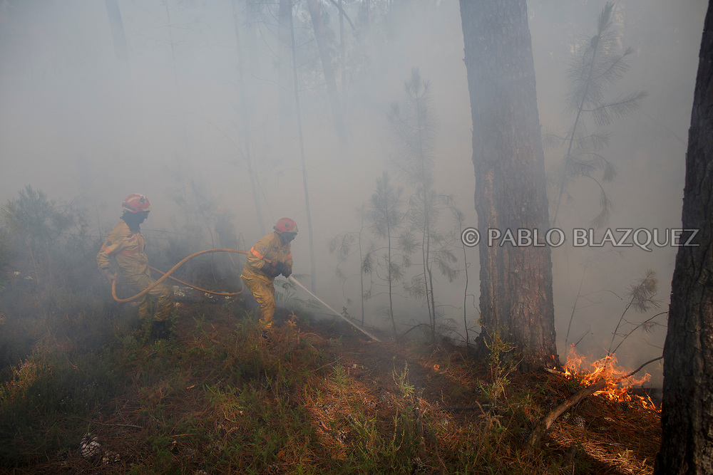 LEIRIA, PORTUGAL - JUNE 19:  Firefighters battle a fire after a wildfire took dozens of lives on June 19, 2017 near Castanheira de Pera, in Leiria district, Portugal. On Saturday night, a forest fire became uncontrollable in the Leiria district, killing at least 62 people and leaving many injured. Some of the victims died inside their cars as they tried to flee the area.  (Photo by Pablo Blazquez Dominguez/Getty Images)