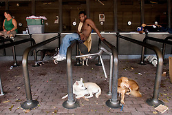 31st August, 2005. New Orleans Louisiana. Hurricane Katrina aftermath.  'Hell on earth.' The Superdome in New Orleans, Louisiana where over 20,000 refugees from hurricane Katrina are crammed into hellish conditions. Men lounge in the shade with the animals they rescued from the storm.<br /> Photo Credit: Charlie Varley/varleypix.com