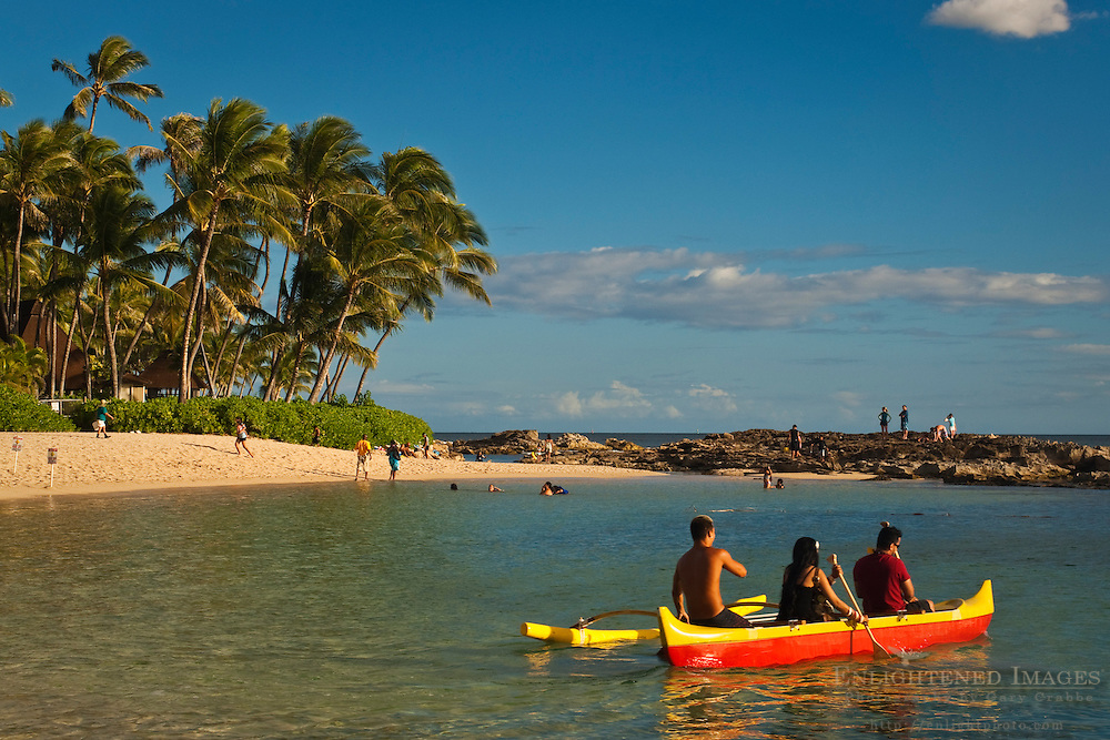Tourists getting a ride in an outrigger canoe at the Paradise Cove Luau, Kapolei, Oahu, Hawaii