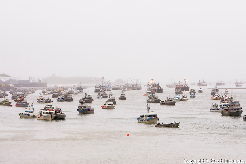 Commercial sockeye salmon fishing gillnet boats at anchor on a foggy evening in the Naknek River in Bristol Bay, Alaska.