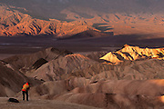 A photographer shoots Zabriskie Point at sunrise.  Death Valley National Monument, California/ Nevada, USA.