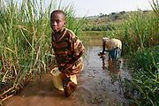 Villages and children collect drinking water  from a swamp off shoot of Akagera river. Near Gatora village. Juru Sector. Bugesera district. Rwanda...© Zute Lightfoot / Water Aid..