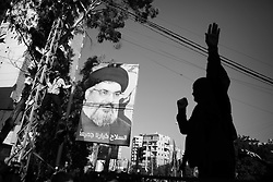 Hassan Nasrallah is popular in south Beirut, where posters justify Hezbollah's arms: 'Weapons are our collective choice'.
