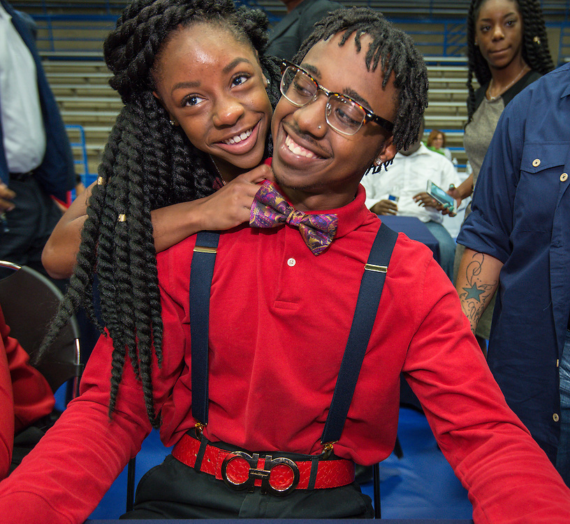 Reagan's Treyvion Waldon gets a hug during National Signing Day ceremonies for Houston ISD student athletes at the Pavilion at Forest Brook Middle School, February 3, 2016.