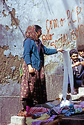 Woman street trader in old housing area of Lisbon, Portugal, 1975 socialist graffiti message on wall