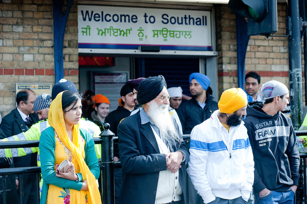 London, UK - 7 April 2013: members of the Sikh community watch the procession outside the Southall train station. The sign is written both in English and Punjabi