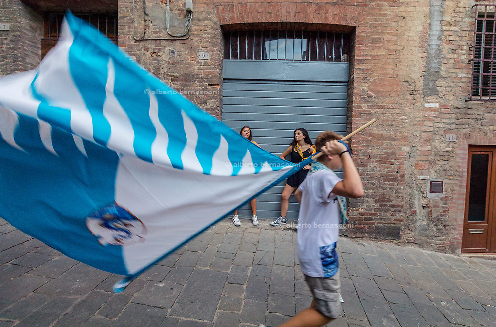 Italy, Siena, the Palio: two teens girls, Acquila supporters clearly disappointed about the winning of thei neighbours of the Onda. supporters of the contrada celebrates in the streets , heading to the contrada where people are waiting for the Palio arrival from thr Duomo.