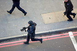 © Licensed to London News Pictures. 29/11/2019. London, UK.  Armed police officers run towards Borough Market following a suspected terror attack on London Bridge. Several people were stabbed, at least two fatally, before armed police shot the attacker dead.  Photo credit: Cliff Hide/LNP