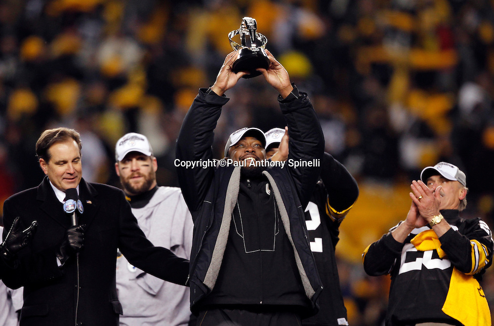 Pittsburgh Steelers head coach Mike Tomlin holds up the AFC Champion Lamar Hunt Trophy during the postgame trophy presentation after winning the NFL 2011 AFC Championship playoff football game against the New York Jets on Sunday, January 23, 2011 in Pittsburgh, Pennsylvania. Tomlin is flanked on the left by sportscaster Jim Nantz and on the right by former Steelers running back Rocky Bleier. The Steelers won the game 24-19. (©Paul Anthony Spinelli)