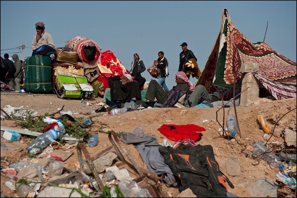 Des réfugiés Egyptiens et Bangladeshi avant leur départ en bus vers le camp humanitaire Choucha situé à quelques kilomètres du poste frontière Ras Jedir. Plus de 140 000 réfugiés ont déjà quitté la Libye par la Tunisie ou l'Egypte et des milliers continuent d'arriver chaque jours. Vendredi 4 Mars 2011, Ras Jedir, Tunisie..© Benjamin Girette/IP3 press