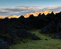 View over Laugahraun lavafield towards Norðurbarmur mountains which are bathed with evening light. Landmannalaugar, Iceland. Horft yfir Laugahraun í átt að Norðurbarmi sem er baðaður kvöldsól.
