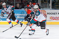 KELOWNA, CANADA - DECEMBER 27:  Tyrell Goulbourne #12 of the Kelowna Rockets handles the puck while checked by Matt Needham C #14 of the Kamloops Blazerson December 27, 2013 at Prospera Place in Kelowna, British Columbia, Canada.   (Photo by Marissa Baecker/Shoot the Breeze)  ***  Local Caption  ***