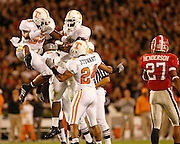 Tennessee defenders, including Jonathan Hefney (33), Antonio Reynolds (89) and Antwan Stewart (24), celebrate a tackle of Georgia return man Mikey Henderson during the game between the Georgia Bulldogs and the Tennessee Volunteers at Sanford Stadium in Athens, GA on October 7, 2006.<br />