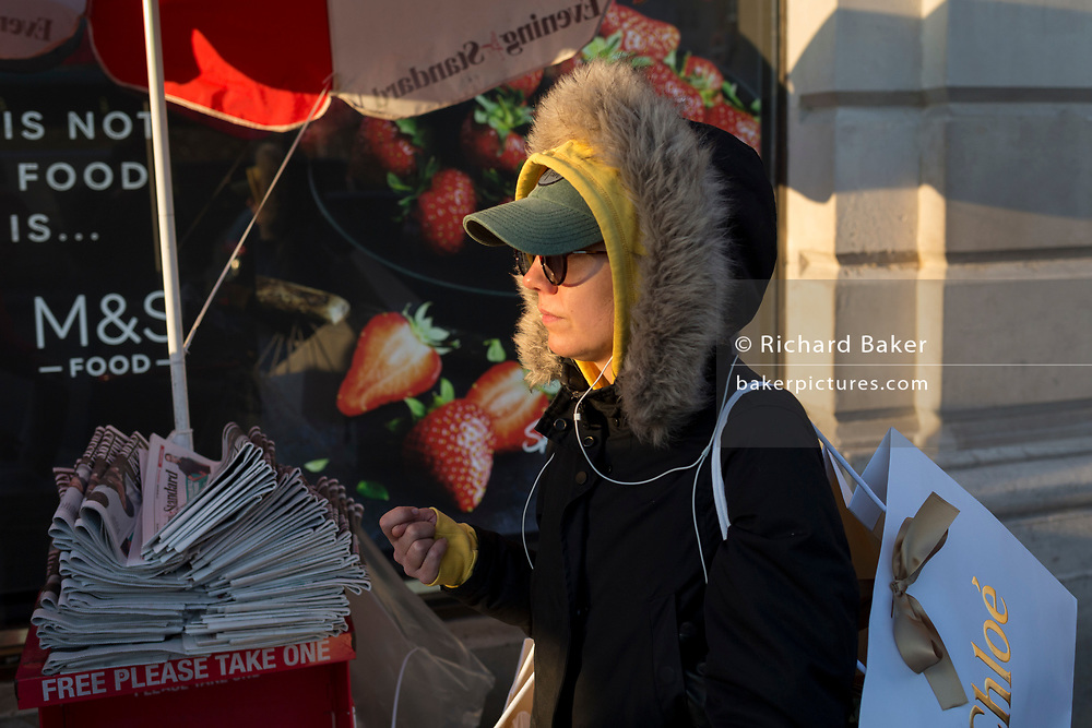 A woman wearing three layers of headwear, walks in the cold on Piccadilly, on 21st January 2020, in London, England.