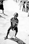 Earthquake in Haiti 2010,A boy with a big can of fresh water from the red cross tanks.