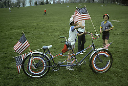 Patriotic youngsters with flag decorated bicycle built for two.