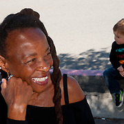 a little boy is sitting on a curb, while his grandmother has a radiant smile of happiness on her face