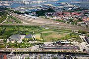 Nederland, Amsterdam, Westerpark, 25-05-2010. Overzicht Cultuurpark Westergasfabriek. Linksonder Staatsliedenbuurt, aan het water de gebouwen van de voormalige fabriek (Zuiveringshal, daarachter Ketelhuis en Machingebouw). Midden het park (architecte Kathryn Gustafson) met de voormalige gashouder. .Het ernstige vervuilde terrein is gesaneerd de voormalige fabrieksgebouwen hebben een culturele bestemming gekregen, het terrein wordt gebruikt voor manifestaties, tentoonstelling, expositie, cultuur, industrieel en cultureel erfgoed: cultuurpark. .Overview Culture Park Westergasfabriek..Left of the canal to Haarlem Staatsliedenbuurt, adjacent to the water the buidling of the former plant. In the middle the park with the former gasometer..The former industrial buildings have a cultural destination, the site is used for events, exhibitions, cultural manifestations: culture park..luchtfoto (toeslag), aerial photo (additional fee required).foto/photo Siebe Swart