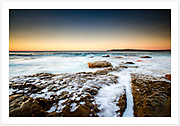 Foam over the weathered rocks around Mahon Pool, early morning looking towards Malabar Headland [Maroubra, NSW, Australia]<br />