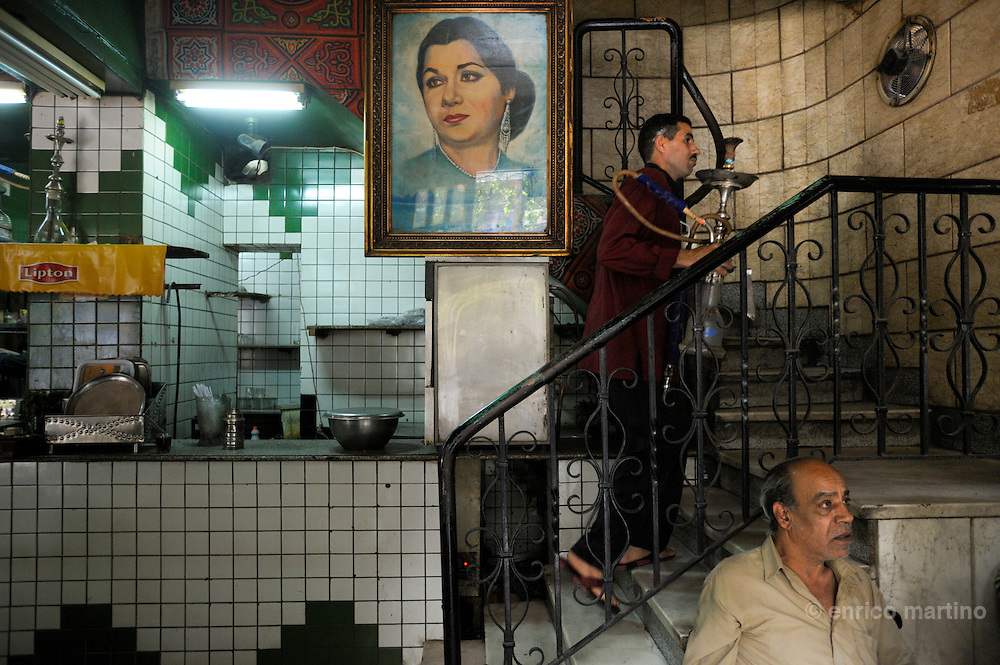 Umm Khaltoum traditional coffe house (ahwa), attended mainly from fans of famous Egyptian singer Oum Kalthoum, whose pictures and memorabilia decorate the walls. Cairo's ahwa (the traditional coffeehouse) are for Cairo what the pub is to London or caffè to Rome. Once the ahwa was the main place for entairnement, a animated place where Cairo's men socialised playing chess, backgammon or domino, reading newspapers or watching TV, drinking Turkish coffee and shai (tea) with mint or smoking a sheesha, the tradional waterpipe. Some ahwa are meeting places for people loving chess or remembering famous Egyptian singer Oum Kalthoum. Today Cairo is changed and everybody is just too busy to drink coffee in a ahwa, so western style coffee shops are much more than traditional ahwa.