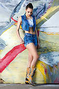 Fashion model Rachael Campbell posing in jeans shorts and vest in front of colorful graffiti wall.