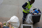 As a visitor eats his takeaway lunch, a council street cleaning contractor adds more waste to his growing binful of rubbish in Trafalgar Square, on 15th June 2019, in London, England.