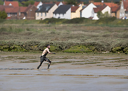 © Licensed to London News Pictures. 12/05/2019. Maldon, UK. A competitor takes an early lead during the Maldon Mud Race in Essex. The race originated in 1973 and involves competitors racing around a course on the mudbanks of the river Blackwater at low tide. Photo credit: Peter Macdiarmid/LNP