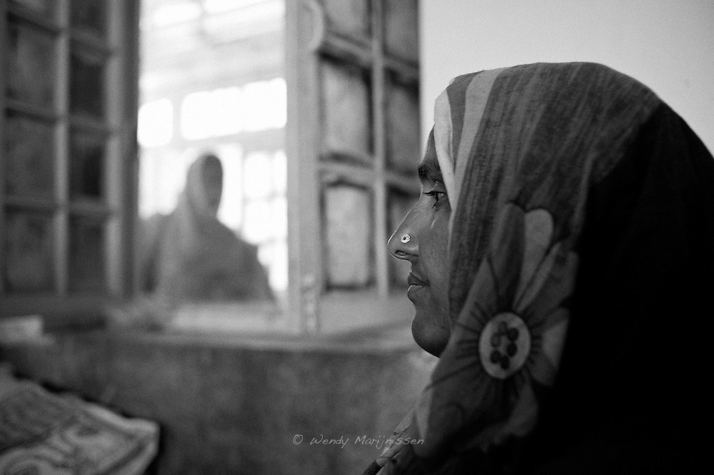 Nazia sits by her daughter Rabia who still recovers from a caesarean section she had the day before. Thari Mirwah, Pakistan, 2010