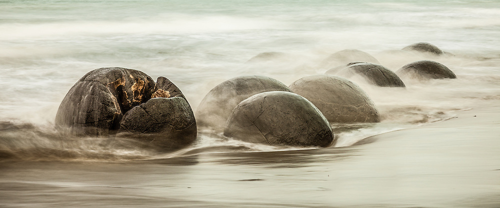 Incoming tide rushing over the Moeraki boulders