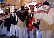 Yemen, Thula, grooms with traditional turbans decorated with flowers standing in line during a wedding.