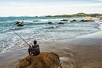 Homem pescando sentado sobre pedra na Praia de Palmas. Governador Celso Ramos, Santa Catarina, Brasil. / Man fishing sitting on a rock at Palmas Beach. Governador Celso Ramos, Santa Catarina, Brazil.