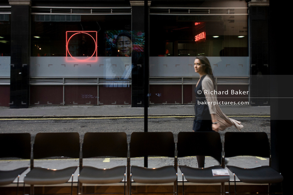 Woman passes-by in a London street and cultural image of female in the background.