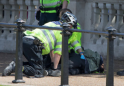 © Licensed to London News Pictures. 24/05/2017. London, UK. Police detain a man opposite Buckingham Palace just before the Changing of the Guard ceremony. Today's ceremonu has been cancelled.  The terrorism threat level has been raised to critical and Operation Temperer has been deployed. 5,000 troops are taking over patrol duties under police command. Photo credit: Peter Macdiarmid/LNP