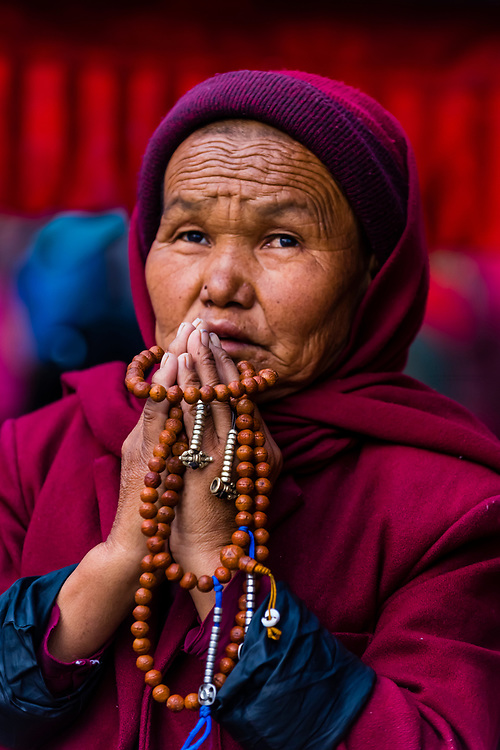 A Buddhist pilgrim praying at the Boudhanath Temple. It is the largest stupa in Nepal and the holiest Tibetan Buddhist temple outside Tibet. It is the center of Tibetan culture in Kathmandu, Nepal.