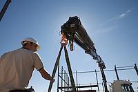 Unloading RSJs (rigid steel joists) from truck to build warehouse