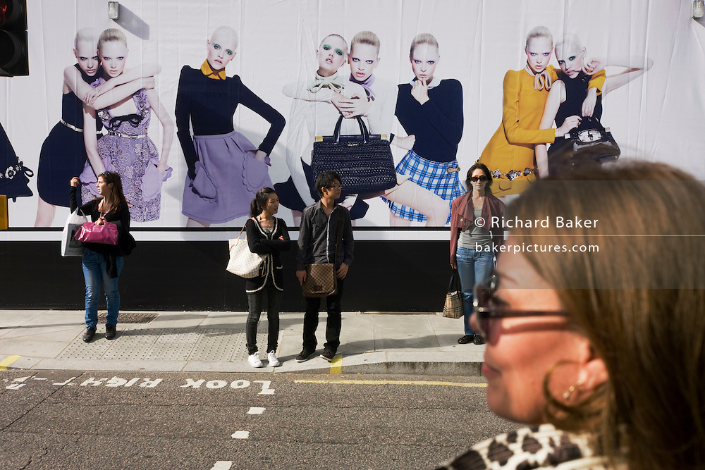 A stylish middle-aged woman is about to cross Bruton Street in London in front of fashion models on an opening soon shop.