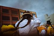 """Maria Eugenia Herrera Mamani, alias """"Claudina The Cursed"""", dances during the carnival in El Alto, Bolivia, February 18, 2012.<br /> <br /> En la ciudad de El Alto - ciudad vecina con La Paz, Bolivia- situada a una altura de 4,000 msnm, turistas y gente local hacen fila para comprar boletos para presenciar el espectáculo de las cholitas luchadoras.  Cada domingo un grupo de mujeres, las """"cholitas"""", se prepara para dar un espectáculo de lucha libre. Ellas portan la ropa tradicional de las mujeres Aymaras, que se ha mantenido desde la época colonial. Su atuendo consiste en faldas amplias, bombines -sombrero típico-, zapatos de plástico, trenzas hasta la cintura, joyas de gran tamaño, maquillaje y chales bordados.<br /> Yenny Wilma Maraz, conocida como """"Marta La Alteña"""", saluda al público con los brazos extendidos bailando al ritmo de la música, entrega su chal y su sombrero para subir al ring. Sube orgullosa aún siendo abucheada por el público. Ella es ruda y tendrá que pelear contra los buenos.<br /> La lucha libre es un espectáculo teatral, pero también requiere de un enorme esfuerzo físico y de entrenamiento constante para poder realizar vuelos desde las cuerdas del ring y soportar las caídas, que muchas veces son dolorosas.<br /> Los eventos de lucha libre son un negocio cada vez mayor. Cientos de turistas y bolivianos, asisten cada semana para ver a las cholitas vencer a sus adversarios. Las cholitas como otros luchadores pertenecen a grupos manejados por diferentes mánager, quienes en muchas ocasiones sacan ventaja, llevándose gran parte de las ganancias y dejando a ellas con casi nada. Esto ha creado divisiones, y por lo tanto, se han conformado nuevos grupos tales como Las Diosas del Ring, quienes ofrecen su espectáculo en diferentes puntos de la ciudad. La lucha libre boliviana ha ganado popularidad y ha traspasado fronteras gracias a las Cholitas luchadoras."""
