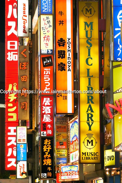 Many bright advertising signs at night in Shinjuku Tokyo